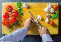 Ο επαγγελματικός αρχιμάγειρας κόβει τα λαχανικά με ένα αιχμηρό μαχαίρι από Damasc Στοκ Φωτογραφία