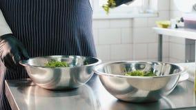 Ο επαγγελματικός αρχιμάγειρας που αναμιγνύει τη σαλάτα παραδίδει κοντά το κύπελλο χάλυβα απόθεμα βίντεο