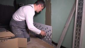 Ο επαγγελματικός εργαζόμενος εγκαθιστά το κεραμικό κεραμίδι στον τοίχο φιλμ μικρού μήκους