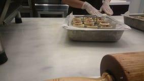 Ο επαγγελματικός ζαχαροπλάστης που μαγειρεύει τα ορεκτικά γλυκά κυλημένα κέικ ψήνει το κατάστημα φιλμ μικρού μήκους