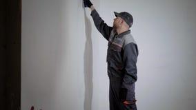 Ο επαγγελματικός ζωγράφος φορά την εργασία ομοιόμορφη και την ΚΑΠ χρωματίζει τον τοίχο από τον κύλινδρο με το άσπρο χρώμα, πλάγια απόθεμα βίντεο