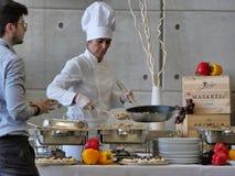 Ο επαγγελματικός θηλυκός αρχιμάγειρας προετοιμάζει τα τρόφιμα μπουφέδων για τους πελάτες στοκ εικόνα