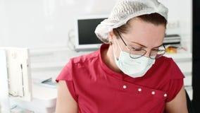 Ο επαγγελματικός θηλυκός οδοντίατρος παρουσιάζει χέρι της στην οθόνη ενός νέου κοριτσιού σε μια οδοντική καρέκλα χρησιμοποιώντας  φιλμ μικρού μήκους