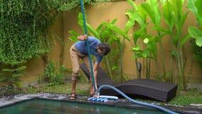 Ο επαγγελματικός καθαριστής πισινών νεαρών άνδρων συγκεντρώνει την καθαρίζοντας υπηρεσία απόθεμα βίντεο