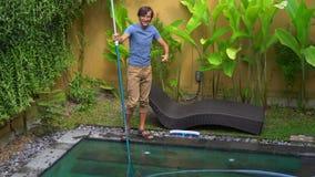 Ο επαγγελματικός καθαριστής πισινών νεαρών άνδρων συγκεντρώνει την καθαρίζοντας υπηρεσία φιλμ μικρού μήκους