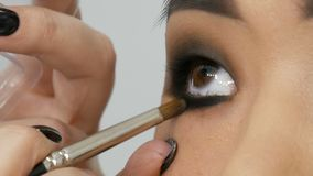 Ο επαγγελματικός καλλιτέχνης σύνθεσης στιλίστων αποτελεί το καπνώές μάτι ενός ασιατικού κοριτσιού να διαμορφώσει το πρόσωπο κατά  απόθεμα βίντεο