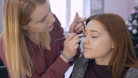Ο επαγγελματικός καλλιτέχνης σύνθεσης το κορίτσι κάνει τη σκίαση των σκιών στο βλέφαρο του πελάτη 4K απόθεμα βίντεο