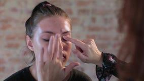 Ο επαγγελματικός καλλιτέχνης makeup γυναικών κινηματογραφήσεων σε πρώτο πλάνο προετοιμάζει το πρόσωπο του νέου χαριτωμένου όμορφο απόθεμα βίντεο
