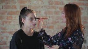 Ο επαγγελματικός καλλιτέχνης makeup γυναικών κινηματογραφήσεων σε πρώτο πλάνο κάνει το πλαστικό κεριών makeup για τον κινηματογρά απόθεμα βίντεο
