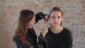 Ο επαγγελματικός καλλιτέχνης makeup γυναικών κινηματογραφήσεων σε πρώτο πλάνο εφαρμόζει το κερί στο πρόσωπο του νέου χαριτωμένου  απόθεμα βίντεο