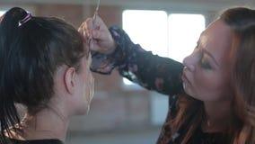 Ο επαγγελματικός καλλιτέχνης makeup γυναικών κινηματογραφήσεων σε πρώτο πλάνο εφαρμόζει το κερί στο πρόσωπο του νέου χαριτωμένου  φιλμ μικρού μήκους