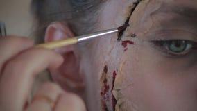 Ο επαγγελματικός καλλιτέχνης makeup γυναικών κινηματογραφήσεων σε πρώτο πλάνο κάνει το πλαστικό κεριών makeup με μορφή αιματηρής  φιλμ μικρού μήκους