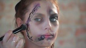 Ο επαγγελματικός καλλιτέχνης makeup γυναικών κινηματογραφήσεων σε πρώτο πλάνο κάνει το πλαστικό κεριών makeup με μορφή αιματηρής  απόθεμα βίντεο