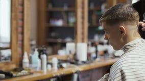 Ο επαγγελματικός κουρέας κάνει το σύγχρονο hairstyle για το νέο καυκάσιο τύπο φιλμ μικρού μήκους