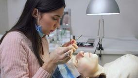Ο επαγγελματικός κύριος κάνει eyelash την επέκταση σε μια νέα γυναίκα απόθεμα βίντεο
