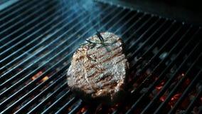 Ο επαγγελματικός μάγειρας γυρίζει το κομμάτι του κρέατος στη σχάρα στην κουζίνα στο εσωτερικό απόθεμα βίντεο