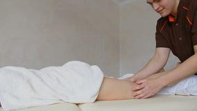 Ο επαγγελματικός μασέρ ζυμώνει τα πόδια του ασθενή κοριτσιών, ο οποίος βρίσκεται στον καναπέ στο φωτεινό γραφείο φιλμ μικρού μήκους
