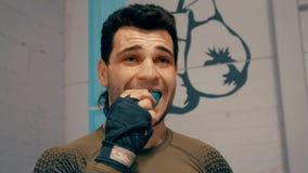 Ο επαγγελματικός μαχητής παρεμβάλλει το επιστόμιο στο στόμα του προετοιμαμένος να παλεψει στη θέση κοντά στο ριγκ απόθεμα βίντεο