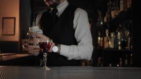 Ο επαγγελματικός μπάρμαν στο σκοτεινό αναμμένο φραγμό προετοιμάζει το ποτό απόθεμα βίντεο