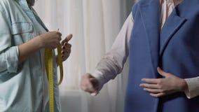 Ο επαγγελματικός ράφτης που μετρά το μήκος του βραχίονα πελατών παρουσιάζει δωμάτιο, επιχείρηση απόθεμα βίντεο