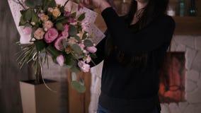 Ο επαγγελματικός floral καλλιτέχνης γυναικών, ανθοκόμος τυλίγει τα λουλούδια - ρόδινα τριαντάφυλλα στο έγγραφο δώρων στο εργαστήρ απόθεμα βίντεο