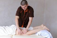 Ο επαγγελματικός αρσενικός μασέρ ζυμώνει τα πόδια του κοριτσιού στον ασθενή, ο οποίος λι Στοκ Φωτογραφία