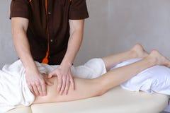 Ο επαγγελματικός αρσενικός μασέρ ζυμώνει τα πόδια του κοριτσιού στον ασθενή, ο οποίος λι Στοκ εικόνες με δικαίωμα ελεύθερης χρήσης