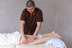 Ο επαγγελματικός αρσενικός μασέρ ζυμώνει τα πόδια του κοριτσιού στον ασθενή, ο οποίος λι Στοκ Εικόνες