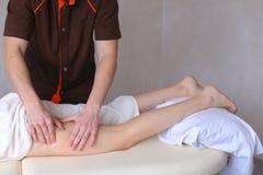 Ο επαγγελματικός αρσενικός μασέρ ζυμώνει τα πόδια του κοριτσιού στον ασθενή, ο οποίος λι Στοκ Φωτογραφίες
