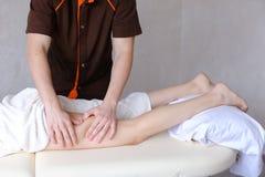 Ο επαγγελματικός αρσενικός μασέρ ζυμώνει τα πόδια του κοριτσιού στον ασθενή, ο οποίος λι Στοκ φωτογραφία με δικαίωμα ελεύθερης χρήσης