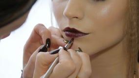 Ο επαγγελματικός καλλιτέχνης makeup απευθύνεται makeup σε ένα όμορφο πρότυπο Χρώματα του κόκκινου κραγιόν Κινηματογράφηση σε πρώτ απόθεμα βίντεο