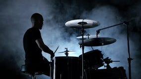 Ο επαγγελματικός μουσικός παίζει τη μουσική στα τύμπανα ανασκόπηση καπνώδης Πλάγια όψη σκιαγραφία πίσω φως κίνηση αργή απόθεμα βίντεο