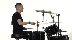 Ο επαγγελματικός μουσικός παίζει τη μουσική στα τύμπανα με τη βοήθεια των ραβδιών Άσπρη ανασκόπηση Πλάγια όψη κίνηση αργή φιλμ μικρού μήκους