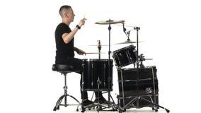 Ο επαγγελματικός μουσικός παίζει τη μουσική στα τύμπανα με τη βοήθεια των ραβδιών Άσπρη ανασκόπηση Πλάγια όψη απόθεμα βίντεο