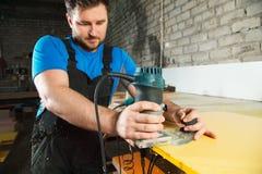 Ο επαγγελματικός ξυλουργός επεξεργάζεται τις πλαστικές άκρες countertop Η έννοια της παραγωγής επίπλων Στοκ φωτογραφία με δικαίωμα ελεύθερης χρήσης