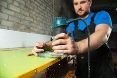Ο επαγγελματικός ξυλουργός επεξεργάζεται τις πλαστικές άκρες countertop Η έννοια της παραγωγής επίπλων Στοκ φωτογραφίες με δικαίωμα ελεύθερης χρήσης