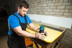 Ο επαγγελματικός ξυλουργός επεξεργάζεται τις πλαστικές άκρες countertop Η έννοια της παραγωγής επίπλων Στοκ Εικόνα