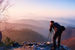 Ο επαγγελματικός φωτογράφος παίρνει τις φωτογραφίες με τη κάμερα καθρεφτών στην αιχμή του βράχου Ονειροπόλο fogy τοπίο, πορτοκαλι Στοκ εικόνα με δικαίωμα ελεύθερης χρήσης