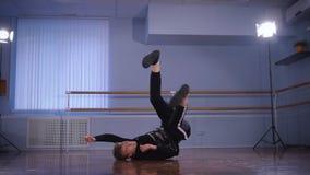 Ο επαγγελματικός χορευτής εκτελεί μη ρεαλιστικά τις βαριές κινήσεις χορού στο πάτωμα σε ένα στούντιο χορού Ισχυρός νεαρός άνδρας  απόθεμα βίντεο