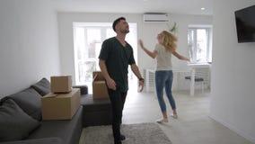 Ο επανεντοπισμός στο νέο σπίτι, ευτυχές ζευγάρι φέρνει τα κιβώτια και απολαμβάνει το νέο διαμέρισμα αγοράς κατά τη διάρκεια του ε φιλμ μικρού μήκους