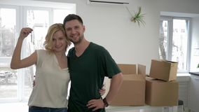 Ο επανεντοπισμός στο νέο σπίτι, πορτρέτο του χαμόγελου του τύπου εραστών με το κορίτσι παρουσιάζει κλειδιά στο διαμέρισμα και το  απόθεμα βίντεο
