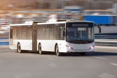 Ο επιβάτης μάκρυνε το αρθρωμένο λεωφορείο πόλεων λεωφορείων των άσπρων γύρων χρώματος με υψηλή ταχύτητα κατά μήκος της εθνικής οδ στοκ φωτογραφία με δικαίωμα ελεύθερης χρήσης