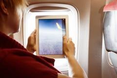 Ο επιβάτης πτήσης που παίρνει τη φωτογραφία ρίχνει το παράθυρο αεροπλάνων στο PC ταμπλετών Στοκ Φωτογραφίες
