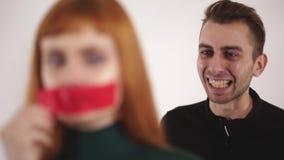 Ο επιθετικός 0 άνδρας φωνάζει στη δεμένη με ταινία γυναίκα, το θηλυκό αφαιρεί το κώλυμα από το στόμα της και την κραυγή από τον π απόθεμα βίντεο
