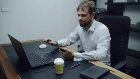 Ο επιθετικός επιχειρηματίας εξετάζει το τηλέφωνο και τον υπολογιστή και ρίχνει επιθετικά έξω ένα ποτήρι του καφέ, άτομο απόθεμα βίντεο