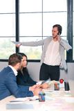 Ο επιθετικός προϊστάμενος μιλά στο κινητό τηλέφωνό του, και κρατά τα έγγραφα στο χέρι του, δίπλα καθίστε δύο εργαζομένους γραφείω Στοκ φωτογραφία με δικαίωμα ελεύθερης χρήσης