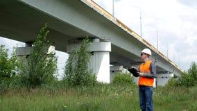 Ο επιθεωρητής γράφει στο φάκελλο και ελέγχει τη θέση της γέφυρας πέρα από τον ποταμό, εφαρμοσμένη μηχανική φιλμ μικρού μήκους