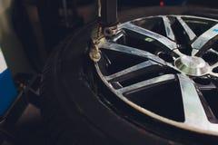 Ο επισκευαστής ισορροπεί τη ρόδα και εγκαθιστά την ασωλήνωτη ρόδα του αυτοκινήτου balancer στο εργαστήριο στοκ φωτογραφία με δικαίωμα ελεύθερης χρήσης