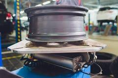 Ο επισκευαστής ισορροπεί τη ρόδα και εγκαθιστά την ασωλήνωτη ρόδα του αυτοκινήτου balancer στο εργαστήριο στοκ εικόνα με δικαίωμα ελεύθερης χρήσης