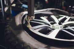 Ο επισκευαστής ισορροπεί τη ρόδα και εγκαθιστά την ασωλήνωτη ρόδα του αυτοκινήτου balancer στο εργαστήριο στοκ εικόνες